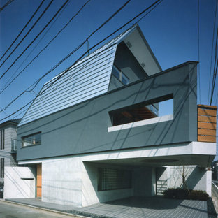 Mid-sized asian stucco grey house exterior in Tokyo with three or more storeys, a shed roof and a metal roof.