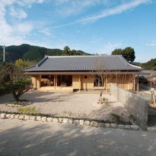 Diseño de fachada de casa beige, asiática, pequeña, de una planta, con revestimiento de estuco, tejado a cuatro aguas y tejado de teja de barro