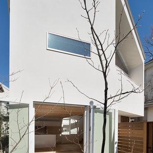 Пример оригинального дизайна: двухэтажный, белый частный загородный дом в стиле шебби-шик с облицовкой из бетона, двускатной крышей и металлической крышей