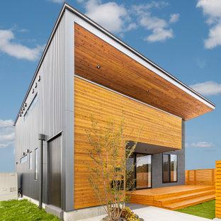 他の地域の中くらいのコンテンポラリースタイルのおしゃれな家の外観 (混合材サイディング、黒い外壁) の写真