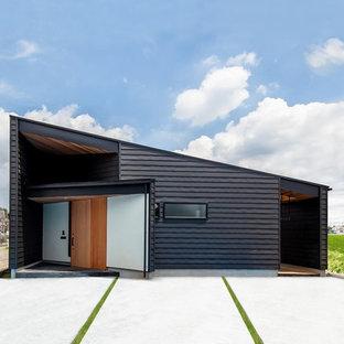 他の地域のコンテンポラリースタイルのおしゃれな陸屋根の家 (黒い外壁) の写真