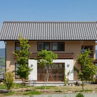 他の地域のアジアンスタイルのおしゃれな家の外観 (ベージュの外壁、切妻屋根、瓦屋根) の写真