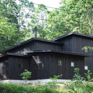 他の地域のコンテンポラリースタイルの家の外観の画像 (木材サイディング、黒い外壁、切妻屋根)