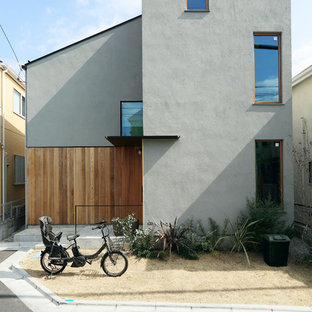 Example of a mid-sized gray two-story stucco house exterior design in Tokyo with a shed roof and a metal roof