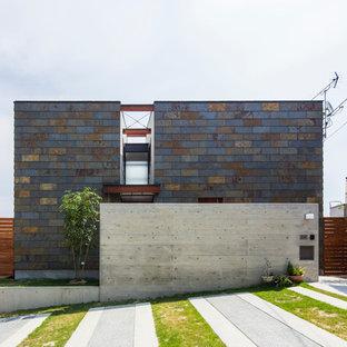 他の地域のコンテンポラリースタイルのおしゃれな二階建ての家 (石材サイディング、マルチカラーの外壁、陸屋根) の写真