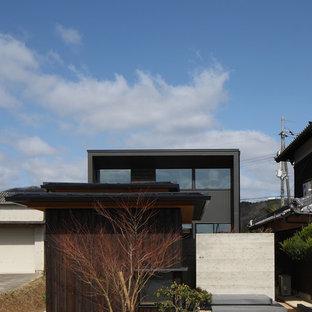 アジアンスタイルのおしゃれな家の外観 (木材サイディング、黒い外壁) の写真