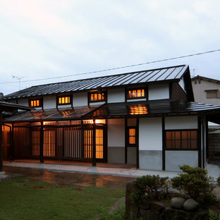 Small asian two-storey stucco white house exterior in Other with a clipped gable roof and a metal roof.