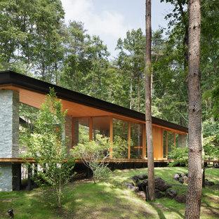 Esempio della facciata di una casa gialla moderna a un piano con rivestimenti misti e tetto a una falda