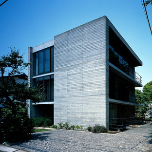 Large asian concrete grey house exterior in Yokohama with three or more storeys and a flat roof.