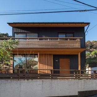 他の地域のアジアンスタイルのおしゃれな切妻屋根の家 (黒い外壁) の写真