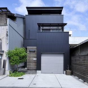 Imagen de fachada de casa negra, contemporánea, de tres plantas, con revestimiento de metal, tejado de un solo tendido y tejado de metal