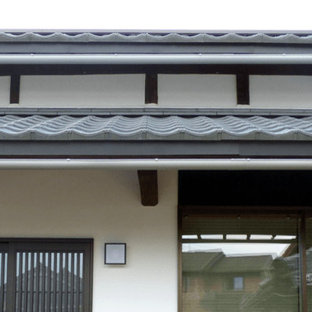 Zen white two-story stucco gable roof idea in Other