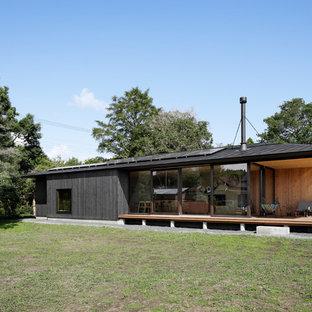 他の地域のアジアンスタイルの平屋の外観の画像 (木材サイディング、黒い外壁、切妻屋根、戸建、金属屋根)