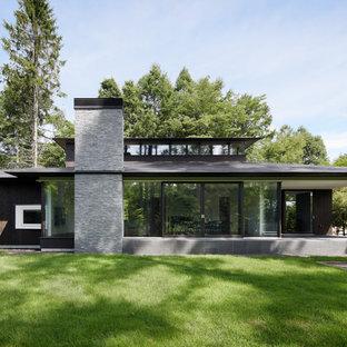 他の地域のトラディショナルスタイルのおしゃれな二階建ての家 (木材サイディング、黒い外壁、寄棟屋根、戸建、金属屋根) の写真