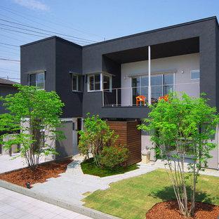 Ejemplo de fachada negra, actual, de dos plantas, con revestimientos combinados y tejado plano
