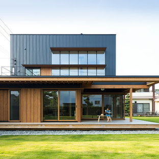 This is an example of a brown contemporary two floor exterior in Other with wood cladding and a flat roof.