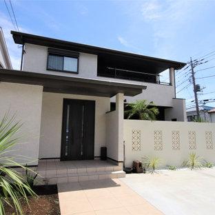 Неиссякаемый источник вдохновения для домашнего уюта: двухэтажный, белый частный загородный дом среднего размера в восточном стиле с облицовкой из крашеного кирпича, двускатной крышей и металлической крышей