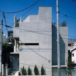 Modelo de fachada de piso multicolor, minimalista, grande, de tres plantas, con revestimiento de hormigón, tejado plano y tejado de varios materiales