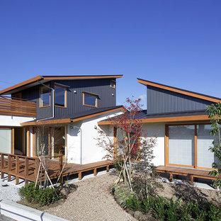 Foto della facciata di una casa nera etnica a due piani con rivestimento in legno e tetto a una falda