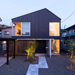 Ejemplo de fachada negra, minimalista, de tamaño medio, de dos plantas, con tejado a dos aguas y revestimientos combinados