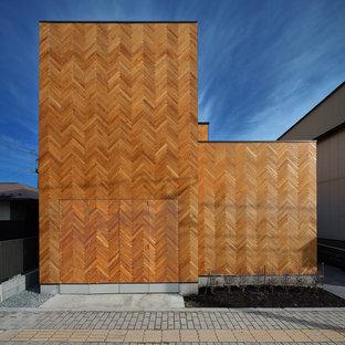 Immagine della facciata di una casa unifamiliare marrone contemporanea a due piani con tetto piano e rivestimento in legno