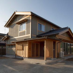 Foto della facciata di una casa unifamiliare nera etnica a due piani di medie dimensioni con rivestimento in legno, tetto a capanna e copertura in tegole