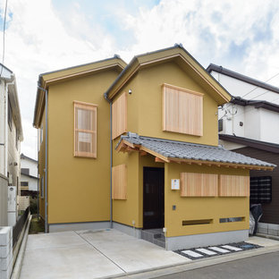 Diseño de fachada de casa beige, asiática, pequeña, de dos plantas, con tejado a dos aguas y tejado de teja de barro