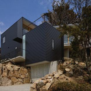 Modelo de fachada de casa azul, minimalista, de tamaño medio, a niveles, con revestimiento de aglomerado de cemento, tejado plano y tejado de metal