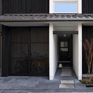 Foto de fachada de casa negra, asiática, pequeña, de dos plantas, con revestimiento de madera, tejado a dos aguas y tejado de teja de barro