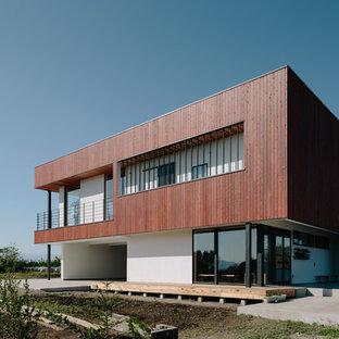 他の地域のコンテンポラリースタイルのおしゃれな二階建ての家 (茶色い外壁、陸屋根) の写真