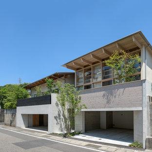 Ejemplo de fachada de casa de estilo zen, de tamaño medio, a niveles, con tejado de metal