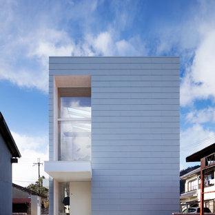 Foto della facciata di una casa unifamiliare bianca moderna a due piani di medie dimensioni con tetto piano, rivestimento in metallo e copertura a scandole