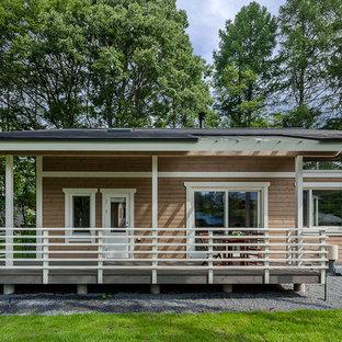 他の地域の北欧スタイルのおしゃれな切妻屋根の家 (木材サイディング、茶色い外壁) の写真