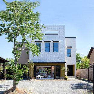 京都の広いモダンスタイルのおしゃれな家の外観 (レンガサイディング、片流れ屋根、戸建、金属屋根) の写真