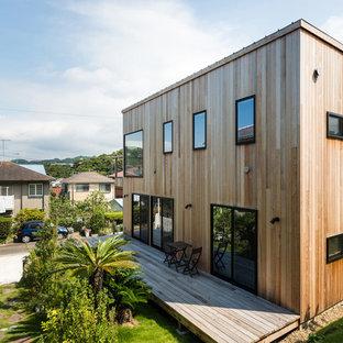 東京都下のコンテンポラリースタイルのおしゃれな二階建ての家 (木材サイディング、茶色い外壁、陸屋根) の写真