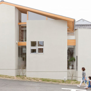 Example of a small danish gray two-story concrete house exterior design in Kyoto with a clipped gable roof and a metal roof