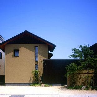 他の地域のアジアンスタイルのおしゃれな二階建ての家 (漆喰サイディング、茶色い外壁、切妻屋根、戸建、金属屋根) の写真