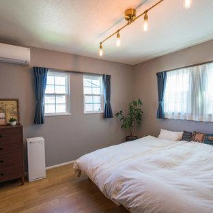 他の地域の中サイズのコンテンポラリースタイルのおしゃれな寝室 (グレーの壁、無垢フローリング、茶色い床)