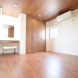 Inspiration för ett funkis huvudsovrum, med vita väggar, plywoodgolv och brunt golv