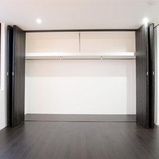 Стильный дизайн: спальня в стиле модернизм с белыми стенами, полом из фанеры и черным полом без камина - последний тренд