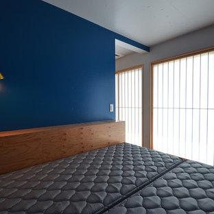 Пример оригинального дизайна: хозяйская спальня в стиле модернизм с синими стенами, полом из фанеры и черным полом