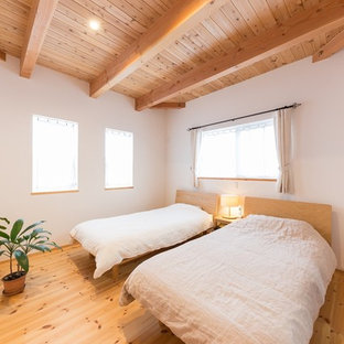 Inspiration for an asian bedroom in Other with white walls, medium hardwood floors and brown floor.