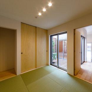Diseño de habitación de invitados minimalista con paredes blancas, tatami y suelo verde