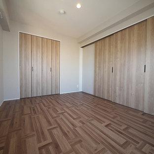 Foto de habitación de invitados industrial con paredes beige, suelo de contrachapado y suelo marrón