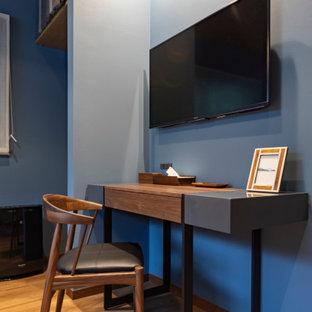 Idee per una piccola camera matrimoniale moderna con pareti blu, pavimento in compensato e pavimento marrone