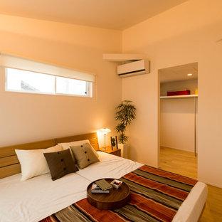 他の地域, のコンテンポラリースタイルのおしゃれな寝室 (白い壁、無垢フローリング、茶色い床) のレイアウト
