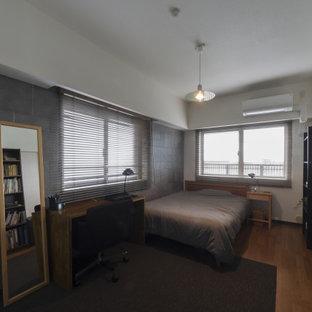 Imagen de dormitorio principal, minimalista, de tamaño medio, sin chimenea, con paredes blancas, suelo de contrachapado y suelo marrón