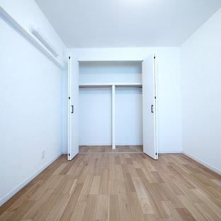 Foto di una camera matrimoniale rustica con pareti bianche, pavimento in compensato e pavimento beige