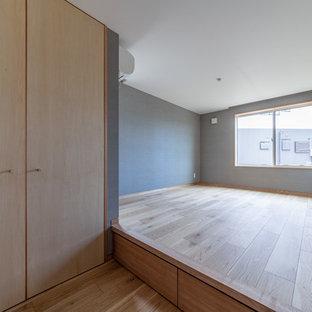 Foto på ett orientaliskt huvudsovrum, med bruna väggar och plywoodgolv