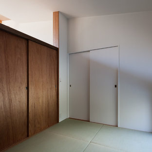 Example of a guest tatami floor bedroom design in Other with white walls